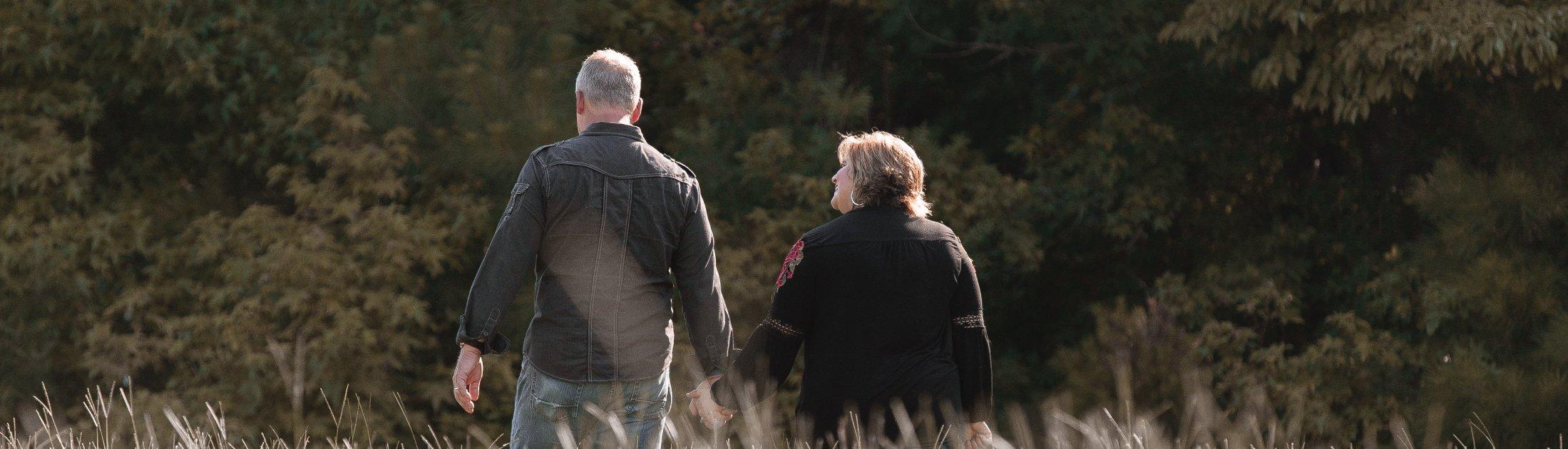 Dan & Melodie Griffin walking in field
